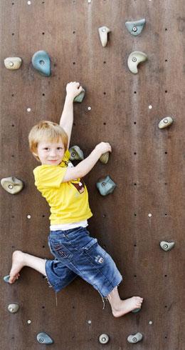 Junge in einer Kletterwand